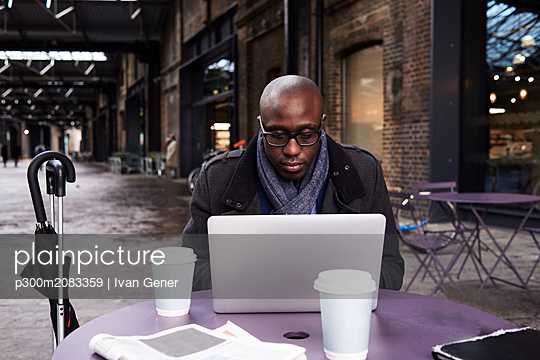 Portrait of businessman working on laptop at coworking space - p300m2083359 by Ivan Gener