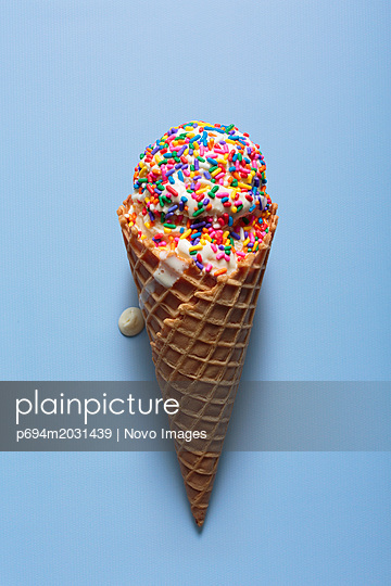 Melting Ice Cream in Cone with Rainbow Sprinkles Against Blue Background - p694m2031439 by Novo Images