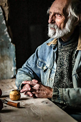 Senior man in rustic room at Table with Apples - p1019m2135198 by Stephen Carroll