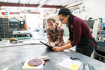 Two women standing at workbench in metal workshop, looking at digital tablet. - p1100m1544244 by Mint Images