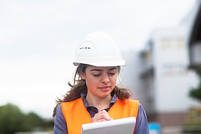Female worker with clipboard taking notes on industrial site - p300m2155744 by Sigrid Gombert