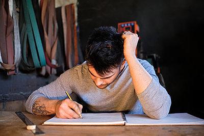 Craftsman drawing on book at workshop - p300m2281489 by Antonio Ovejero Diaz