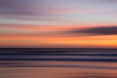 Defocused view of ocean waves on beach under sunset sky - p555m1411725 by Sam Diephuis