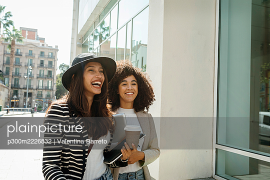Happy female coworkers standing on street in city during sunny day - p300m2226832 by Valentina Barreto