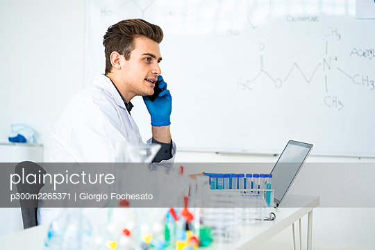 Male scientist talking on mobile phone while sitting at desk in laboratory - p300m2265371 by Giorgio Fochesato