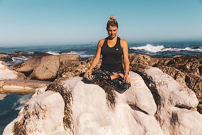 Junge Frau meditiert auf einem Felsen am Meer - p1640m2261155 von Holly & John