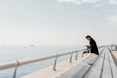 Businessman sitting on quay wall checking cell phone - p300m2102201 by VITTA GALLERY