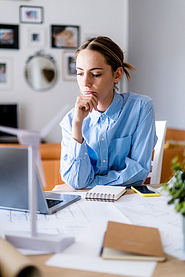 Woman in office working on plan and laptop with wind turbine model on table - p300m2114288 by Giorgio Fochesato