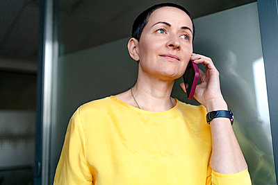 Beautiful female professional talking on mobile phone in office - p300m2276994 by Oxana Guryanova