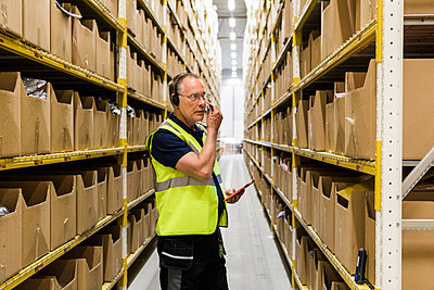 Senior male worker with digital tablet looking at packages on rack while talking through headset at distribution warehou - p426m2018829 by Maskot