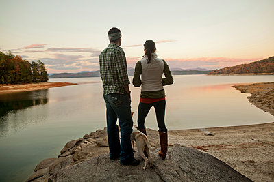 Couple and dog admiring remote lake - p555m1410842 by Aaron Greene