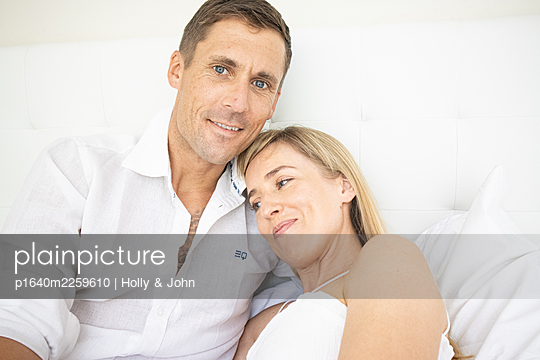 Happy couple sitting on bed, portrait - p1640m2259610 by Holly & John