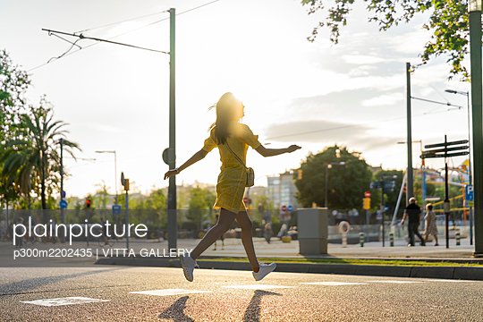 Young woman running on city street during sunny day - p300m2202435 by VITTA GALLERY
