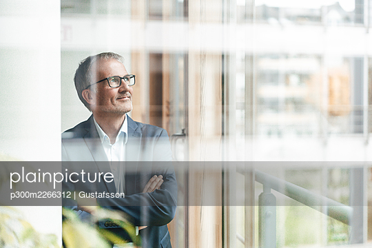 Smiling senior male entrepreneur with arms crossed looking through window in office - p300m2266312 by Gustafsson