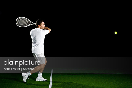 A tennis player about to a hit a ball, studio shot, portrait