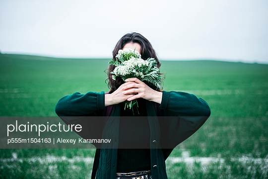 Caucasian woman holding wildflowers in front of face - p555m1504163 by Alexey Karamanov