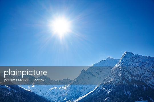 Sonne über verschneiter Bergkette - p851m1148586 von Lohfink