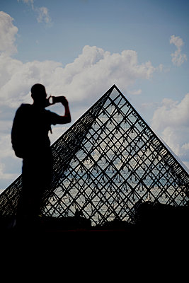 Young man taking pictures of the Louvre Pyramid, Paris - p1028m2150514 by Jean Marmeisse