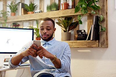 Male illustrator using smart phone in creative office - p1166m1142899 by Cavan Images
