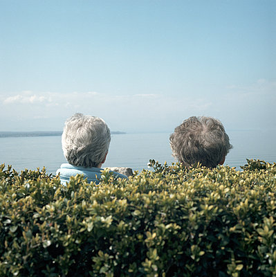 Two female seniors looking out over the sea - p1468m1558916 by Philippe Leroux