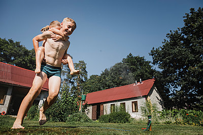 Brother and sister playing with garden hose in garden - p300m2042392 von Katharina Mikhrin
