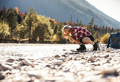 Austria, Alps, woman on a hiking trip having a break at a brook - p300m2081315 by Uwe Umstätter