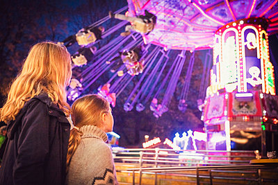 Blond siblings looking at illuminated chain spring ride in motion. Munich, Germany - p300m2197720 by Studio 27