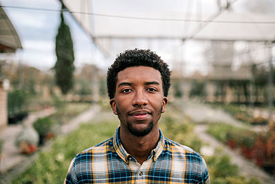Young African male farmer at plant nursery - p300m2240645 by LUPE RODRIGUEZ