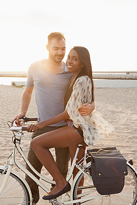 Couple with bicycle on beach - p555m1480184 by Hello Lovely