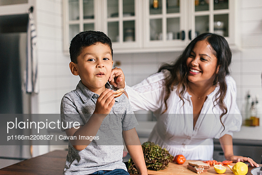 Mother and son having fun together while eating sandwiches in kitchen - p1166m2208527 by Cavan Images