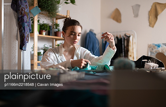 Focused female tailor sewing clothes - p1166m2218548 by Cavan Images