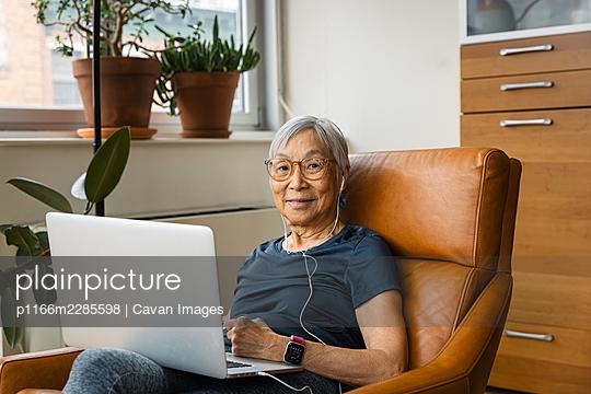 Portrait of senior woman wearing earphones while using laptop at home - p1166m2285598 by Cavan Images