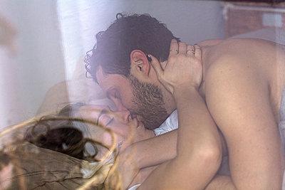 Pärchen liegt aufeinander im Bett und küsst sich  - p1301m1424721 von Delia Baum