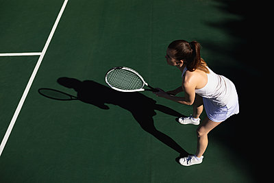 Woman playing tennis on a sunny day - p1315m2131511 by Wavebreak