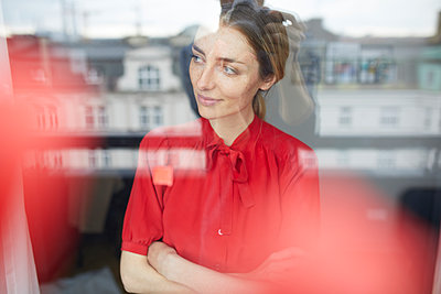 Portrait of smiling woman behind windowpane wearing red blouse - p300m1580700 von Philipp Nemenz