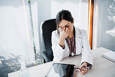 Tired female doctor at desk in medical clinic - p300m2265030 by Eva Blanco