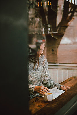 Young woman reading book and drinking espresso at cafe window - p301m2213629 by Toby Mitchell