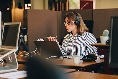 Mature businesswoman wearing headphones while talking on mobile phone in office - p426m2032490 by Maskot