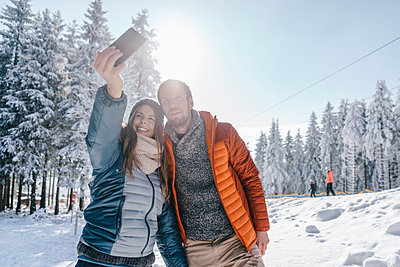 Young couple in winter clothing takes a selfie - p586m2005121 by Kniel Synnatzschke