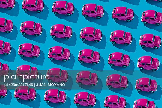Mosaic of pink toy cars on a blue background - p1423m2217646 von JUAN MOYANO
