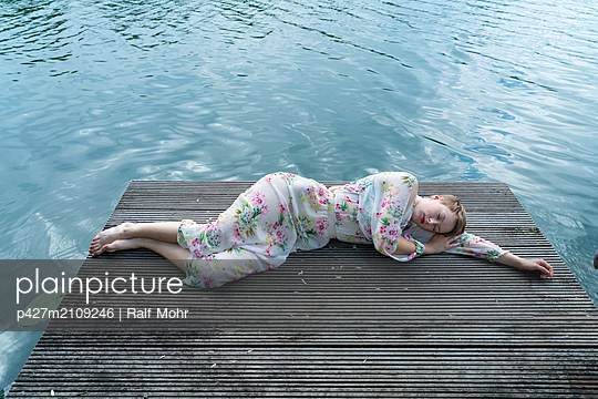 Woman sleeping by the lake - p427m2109246 by Ralf Mohr