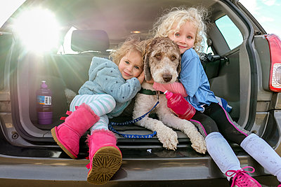 Portrait of smiling sisters embracing dog sitting in car trunk - p1166m1543922 by Cavan Images