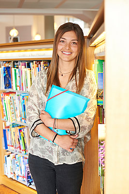 Portrait of smiling young woman with folder leaning against bookshelf in the library - p300m2029293 by Ivan Gener