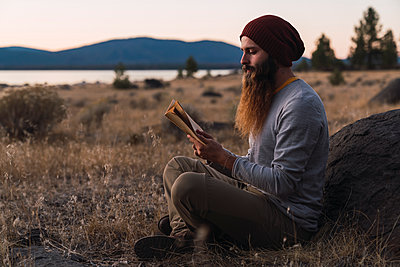 USA, North California, bearded young man reading a book near Lassen Volcanic National Park - p300m2059022 by Kike Arnaiz