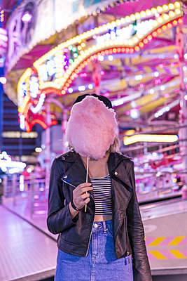 Teenage girl hiding her face behind pink candyfloss at fair - p300m2069752 by Francesco Buttitta