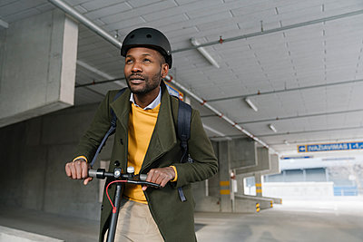 Portrait of stylish man with helmet and scooter in the city - p300m2155249 von Hernandez and Sorokina
