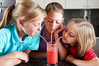 Girls drinking fruit juice with straws - p42911805f by Adie Bush