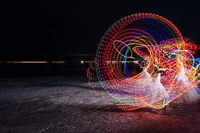 Woman dancing with illuminated multi-coloured hoop at night - p429m1105794 by Pete Saloutos