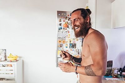 Bearded tattooed shirtless man with long brunette hair standing in a kitchen, laughing. - p429m2201635 by Eugenio Marongiu