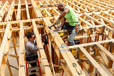 Man and woman hammering frame at construction site - p555m1522812 by Roberto Westbrook